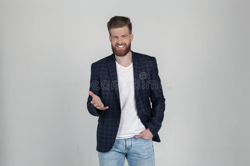 A beautiful sexy bearded man in a jacket has positive expression, points with index finger to the camera. he stands in front of stock photography