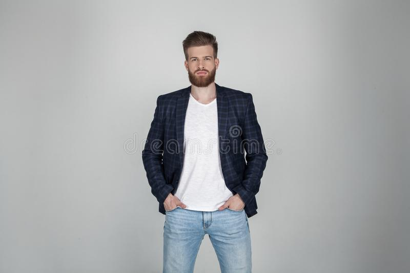 A beautiful sexy bearded man in a jacket holds his hands on his jeans and looks at the camera. he stands in front of the white stock photography