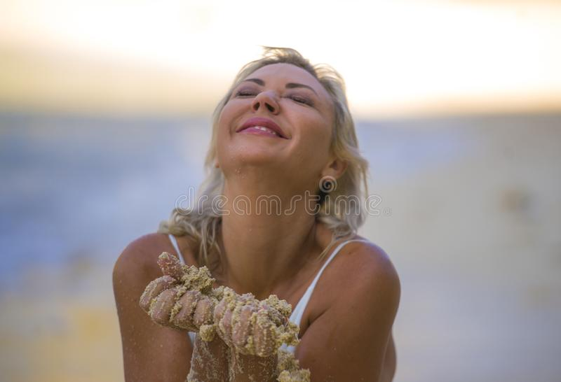 Beautiful and sexy blond hair woman in bikini posing happy and relaxed at tropical beach in holidays getaway trip playing with wet stock photo