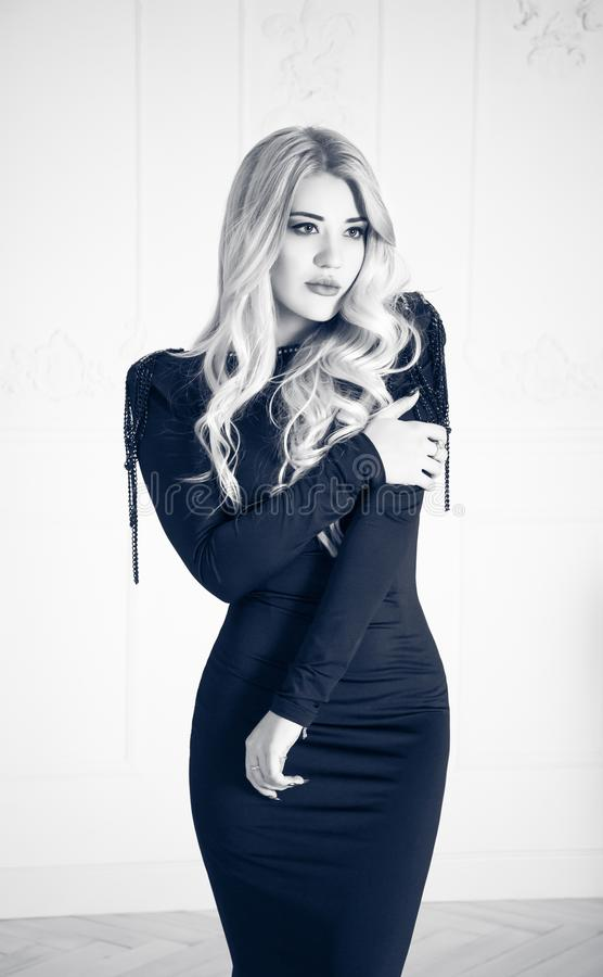 Beautiful blonde in black dress posing on white background. Elegant young woman. stock photos