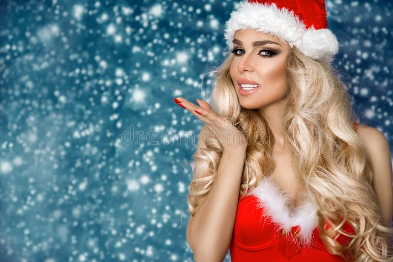 Beautiful blonde female model dressed in a Santa Claus hat and dress. Sensual girl for Christmas stock photos