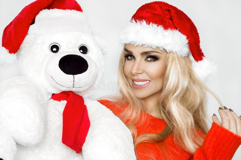 Beautiful blonde female model dressed in a Santa Claus hat embraces a white teddy bear in a red cap Christm stock images
