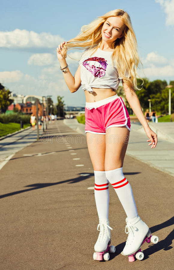 Beautiful blonde girl posing on a vintage roller skates in pink shorts and white T-shirt in the skate park on a warm summer e royalty free stock photos