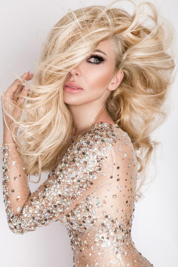 Beautiful blonde model with amazing eyes, wind down long volume hair with highlights. And sensors perfect face dressed in elegant dress stock image