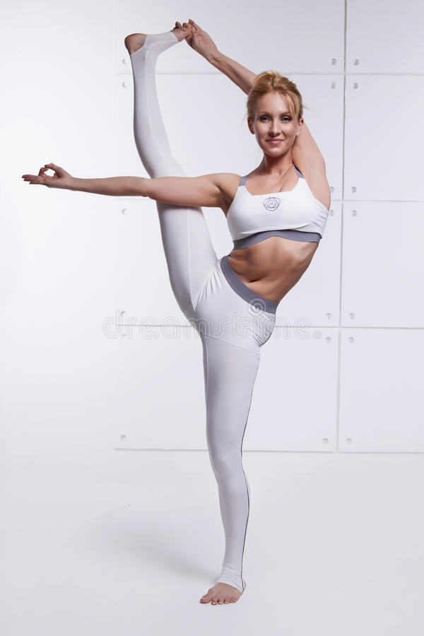 Beautiful blonde perfect athletic slim figure engaged in yoga, exercise or fitness, lead a healthy lifestyle, and eats r royalty free stock photo