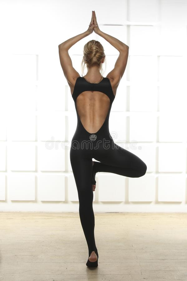 Beautiful blonde with perfect athletic slim figure engaged in yoga, pilates, exercise or fitness, lead healthy lifestyle, and royalty free stock photo