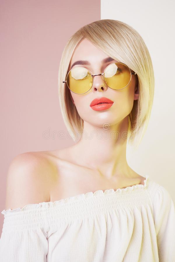 Sensual stylish woman in erotic white dress. Blue-eyed lady with perfect lips in modern colour sunglasses. Beautiful sexy blonde with professional classic make stock photography