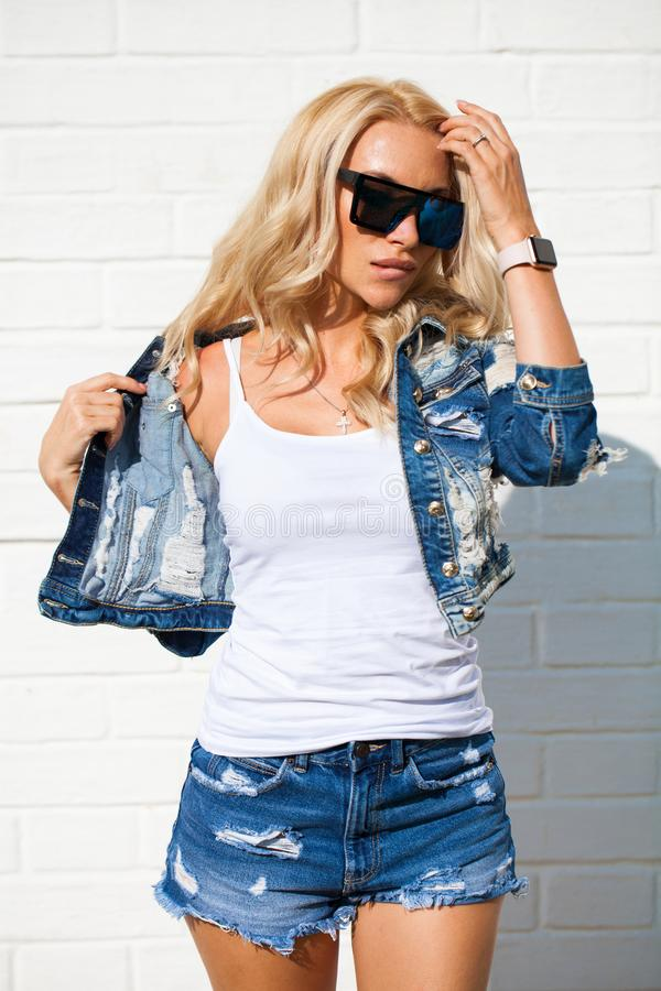 Beautiful blonde woman dressed in a denim jacket and shorts royalty free stock photos