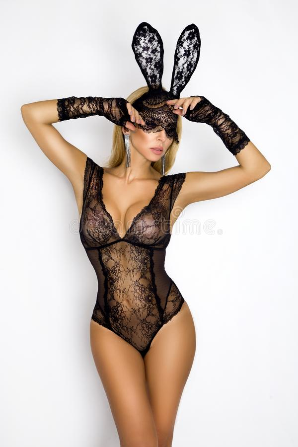 Beautiful, blonde woman in elegant lingerie and black lace Easter bunny mask. Standing on white background stock photo