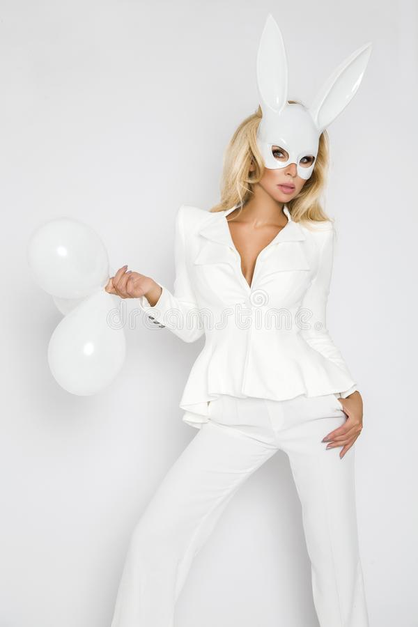 Beautiful, blonde woman girl in elegant white clothes and in a white rabbit mask and baloon stock photography