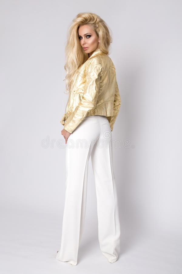 Beautiful blonde woman with long hair standing on a white background dressed in a gold leather jacket biker style royalty free stock photo