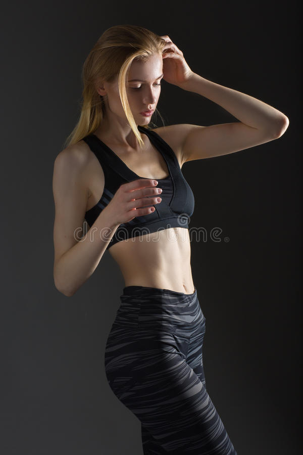 Beautiful blonde woman perfect athletic slim figure engaged in yoga, exercise or fitness, lead healthy lifestyle, eats right, royalty free stock photography