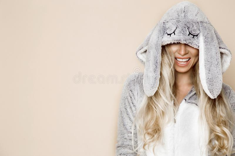 Beautiful blonde woman wearing a pajama, a bunny costume, smiling happily. Fashion model in Easter bun. Beautiful blonde woman wearing a pajama, a bunny costume royalty free stock photo