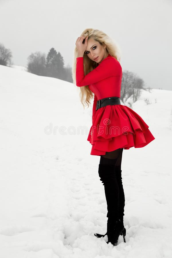 Beautiful blonde woman wearing a red dress and a Santa`s hat in mountains and snow royalty free stock photos