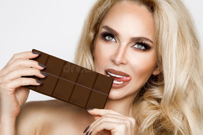 Beautiful, blonde women with green eyes sensually eating tasty chocolate. royalty free stock photo