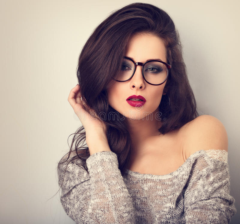 Beautiful bright red lips makeup woman posing in gey blouse. On blue background. CLoseup toned vintage portrait stock image
