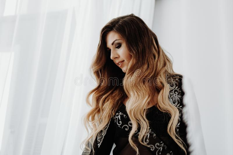 Beautiful sexy brown curly long hair woman posing in bed stock photography
