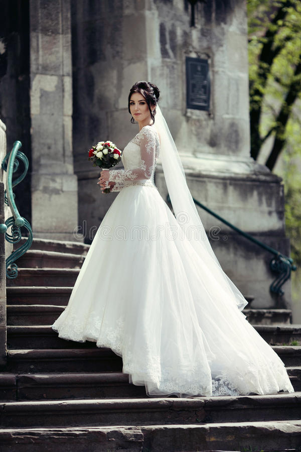 Beautiful brunette bride in white dress walking up stairs, royalty free stock photo