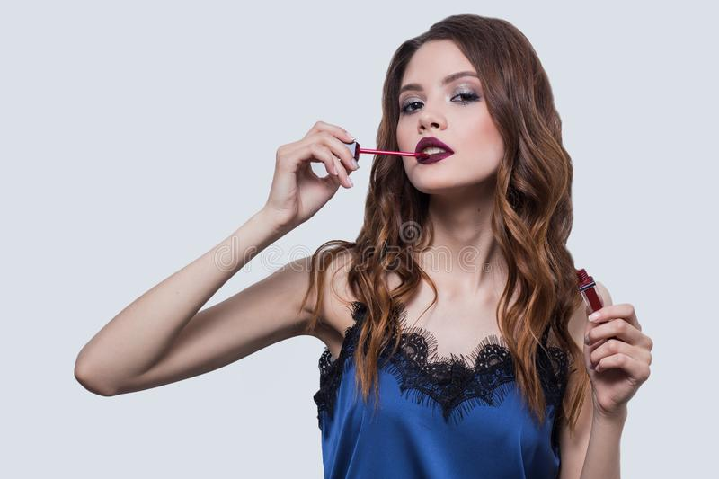Beautiful brunette girl advertises red lipstick, apply lip gloss, looking with parted lips, cosmetics, close-up, white backgr. Ound, blue dress, horizontal stock photo