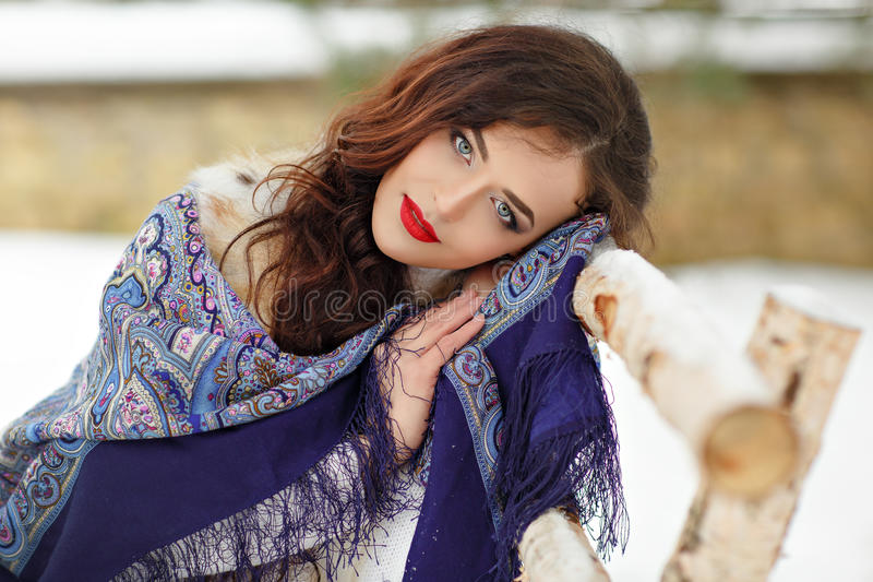 Beautiful brunette girl in a blue scarf in the winter on a. Background of nature sitting on a bench, close up stock image