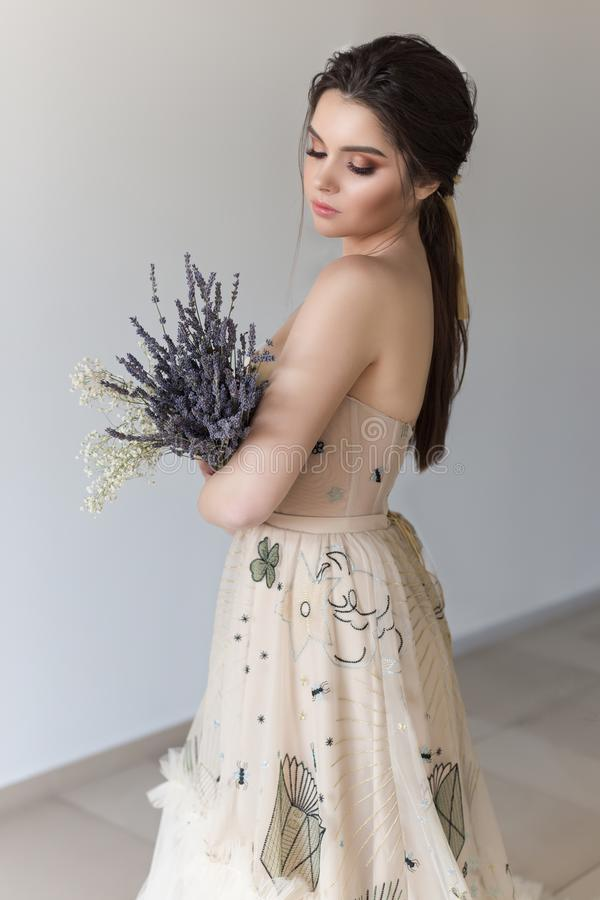 Beautiful brunette girl in elegant dress with long train with lavender flowers royalty free stock photo