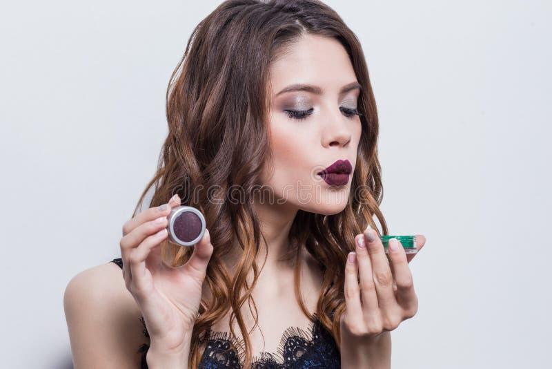 Beautiful, brunette girl with professional make up, bright lips advertises cosmetics, blowing glitter powder, eye shadow, blu stock image