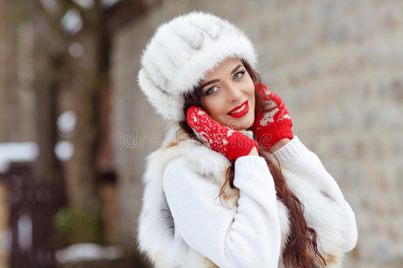 Beautiful brunette girl with red lips in a fur vest and hat. Smiling winter. Close-up stock photos