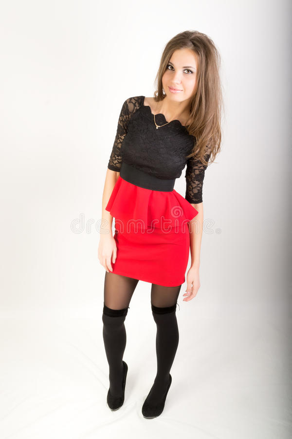 Beautiful brunette girl in red short skirt. Beautiful brunette girl in the studio on a gray background in a red short skirt and stockings royalty free stock photos