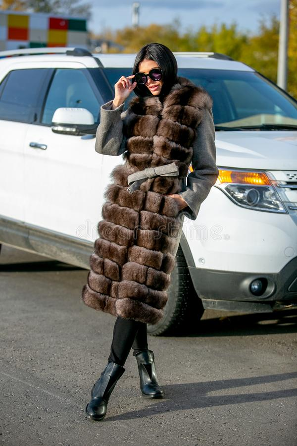Beautiful brunette in sunglasses and a fur coat walks down the street on sunny day and looks away. Late autumn or early winte stock images