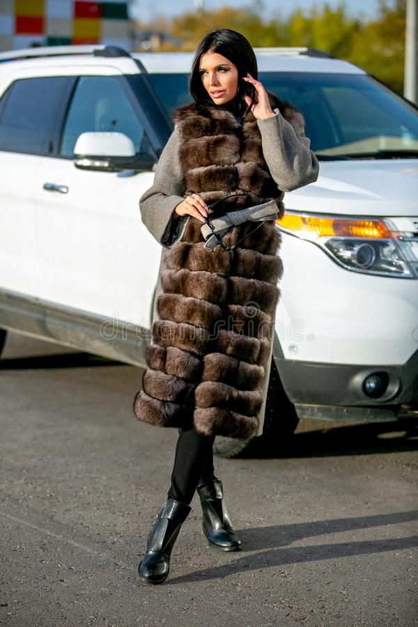 Beautiful brunette in sunglasses and a fur coat walks down the street on sunny day and looks away. Late autumn or early winte stock photo