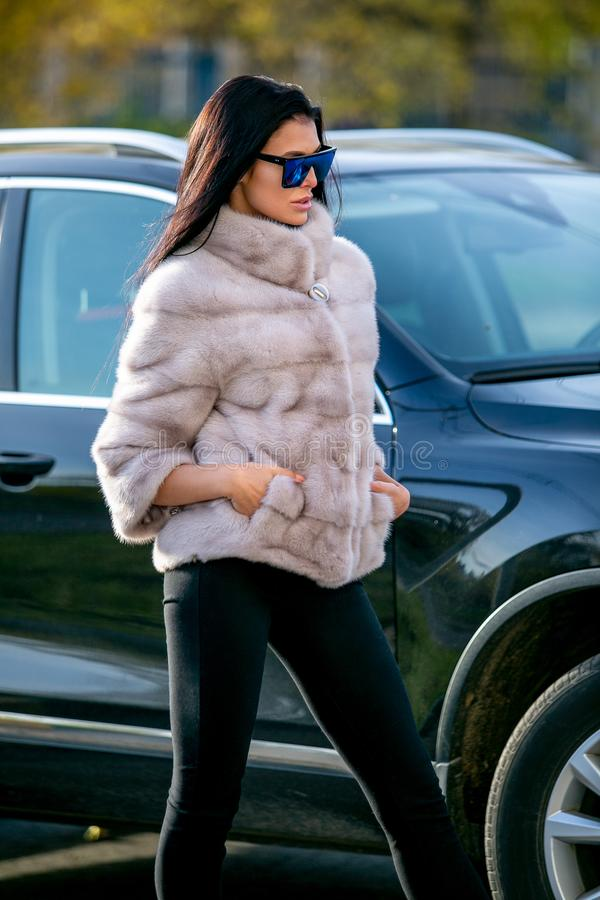 Beautiful brunette in sunglasses and a fur coat walks down the street on sunny day and looks away. Late autumn or early winte royalty free stock photos