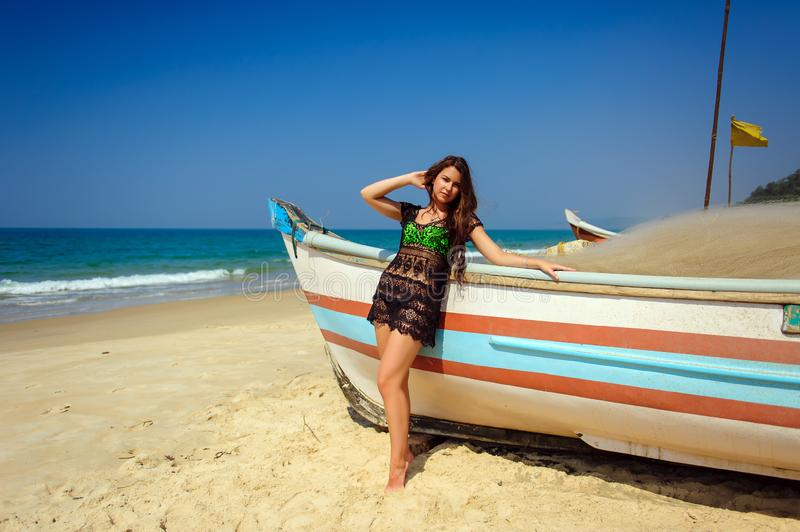 Beautiful sexy brunette on tropical sandy beach near wooden boat on blue sea background and clear sky on hot sunny day. A girl with long hair in a transparent royalty free stock image