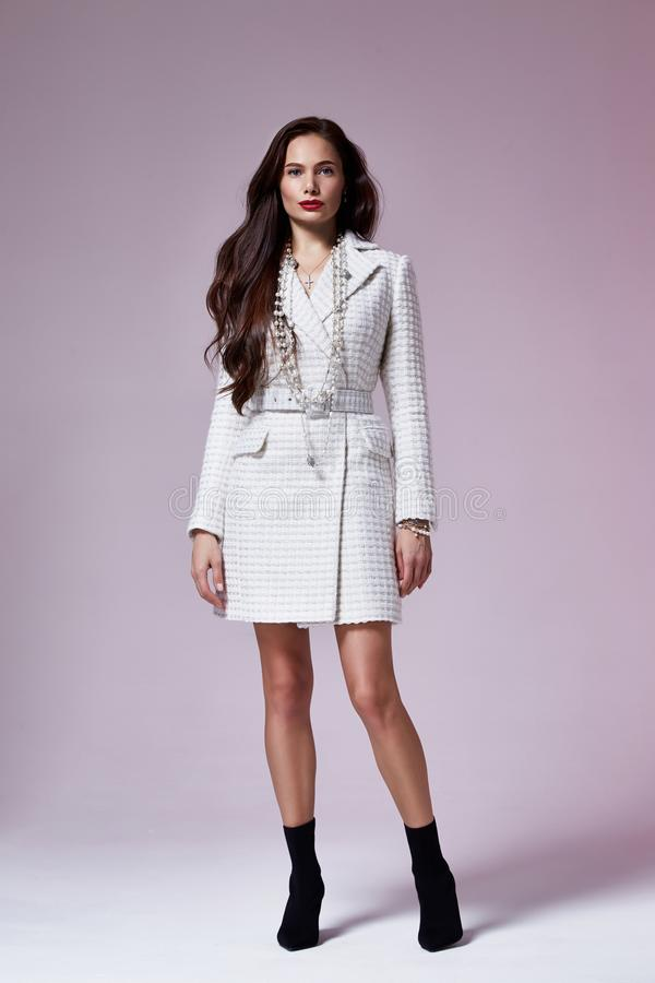 Beautiful brunette woman business office style fashion clothes fall collection perfect body shape pretty face makeup smile. Wear white dress coat casual royalty free stock images