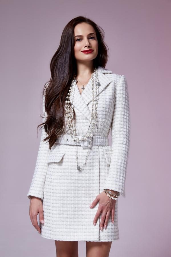 Beautiful brunette woman business office style fashion clothes fall collection perfect body shape pretty face makeup smile. Wear white dress coat casual royalty free stock photo