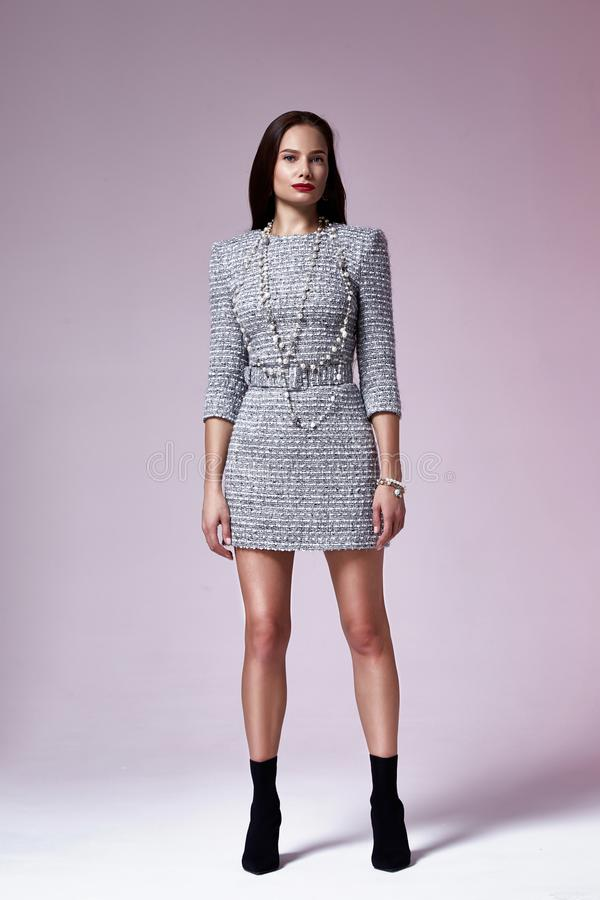 Beautiful brunette woman business office style fashion clothes fall collection perfect body shape pretty face makeup smile. Wear grey dress skinny casual stock photography