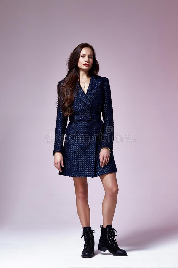 Beautiful brunette woman business office style fashion clothes summer fall collection perfect body shape pretty face makeup. Smile wear dark blue dress coat stock image