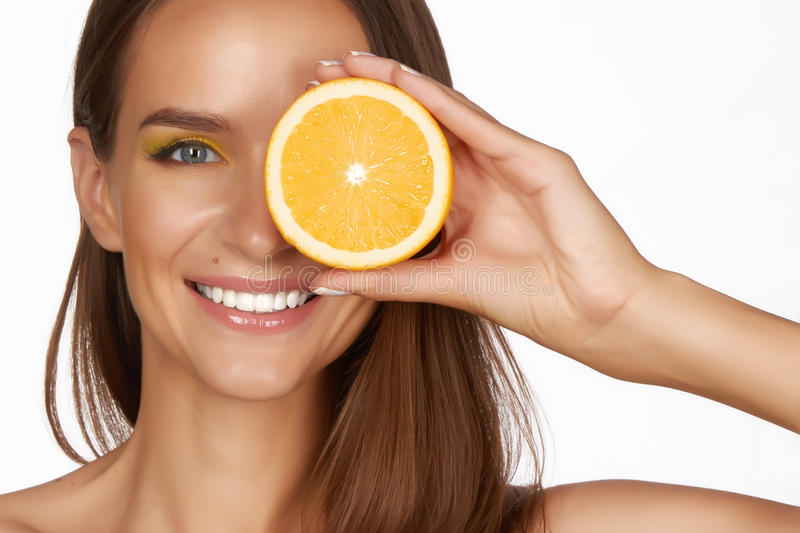 Beautiful brunette woman with citrus on a white background, healthy food, tasty food, organic diet, smile healthy royalty free stock photos