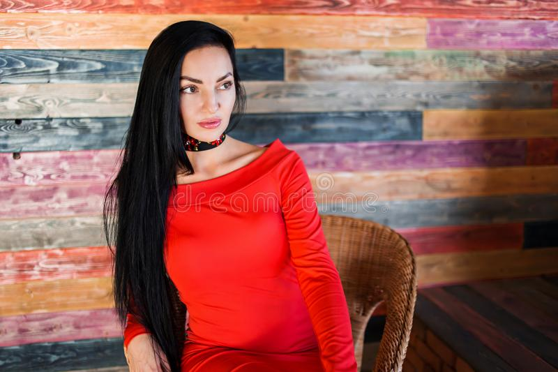 Beautiful brunette woman with makeup and red dress looking away. royalty free stock photos