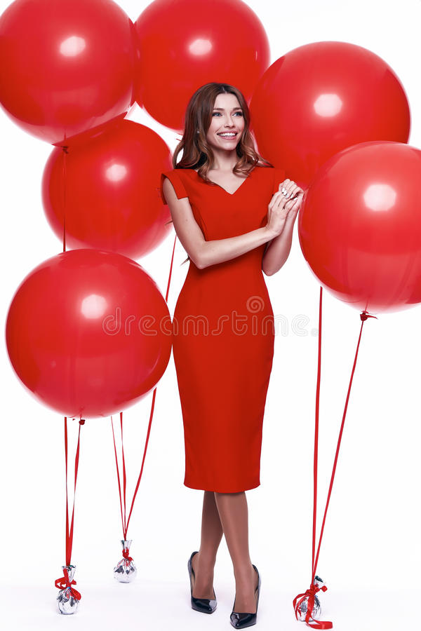 Beautiful brunette woman skinny business style dress. Diplomatic red color perfect body shape busy glamour lady casual style hostess etiquette balloon party royalty free stock images