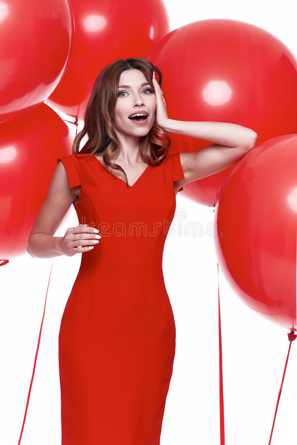 Beautiful brunette woman skinny business style dress. Diplomatic red color perfect body shape busy glamour lady casual style hostess etiquette balloon party royalty free stock photography