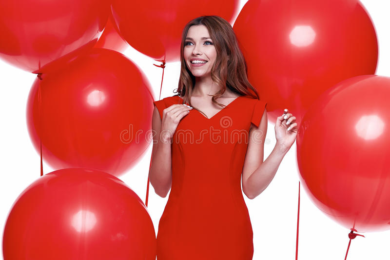 Beautiful brunette woman skinny business style dress. Diplomatic red color perfect body shape busy glamour lady casual style hostess etiquette balloon party stock photography