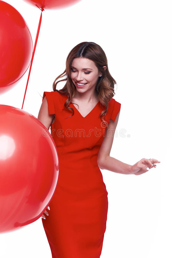 Beautiful brunette woman skinny business style dress. Diplomatic red color perfect body shape busy glamour lady casual style hostess etiquette balloon party stock photo