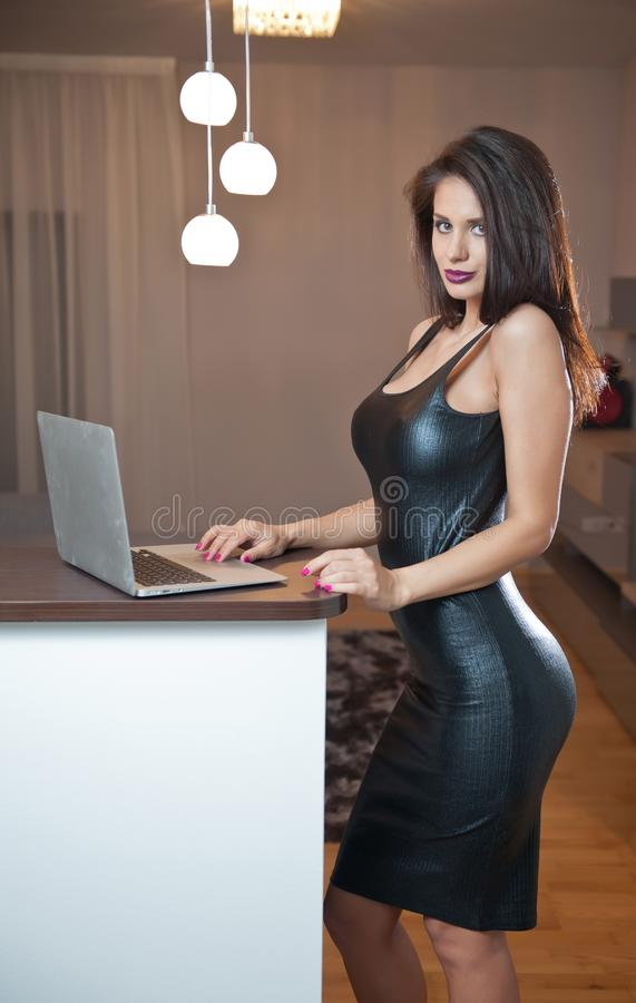 Free Beautiful Sexy Brunette Young Woman With Black Leather Sexy Short Dress And A Laptop. Fashionable Female With Attractive Body Royalty Free Stock Photos - 142444988