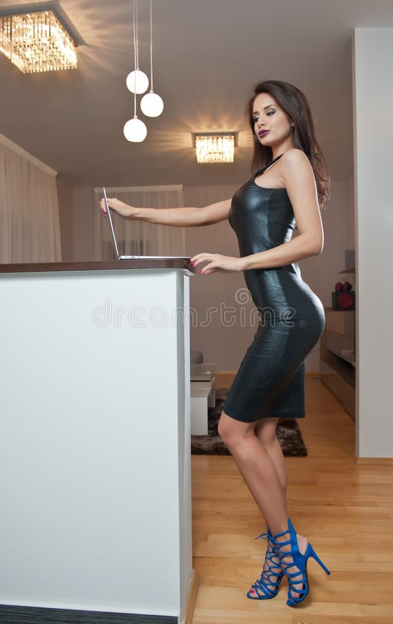 Free Beautiful Sexy Brunette Young Woman With Black Leather Sexy Short Dress And A Laptop. Fashionable Female With Attractive Body Royalty Free Stock Photo - 142629175