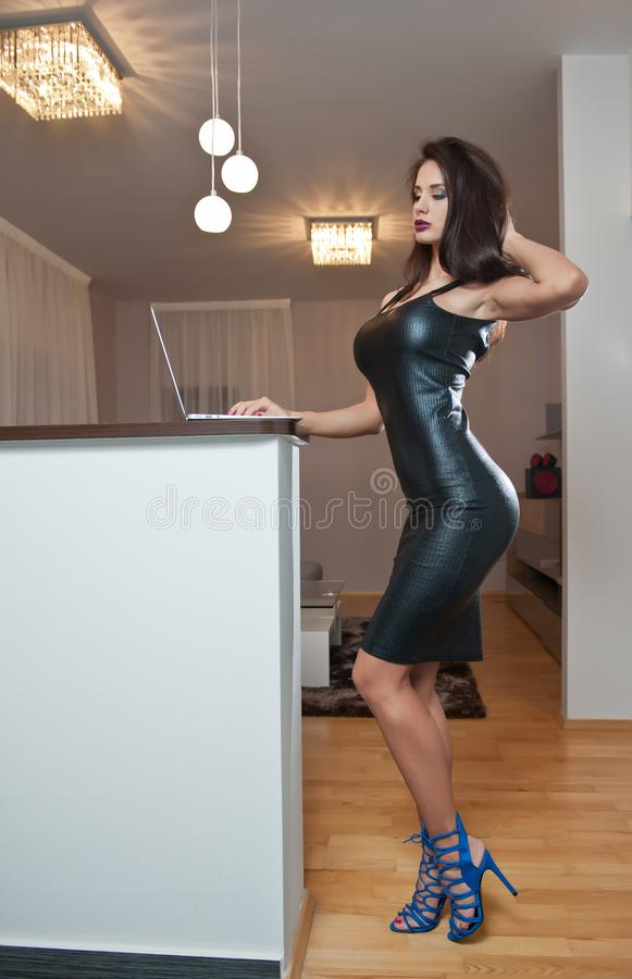 Free Beautiful Sexy Brunette Young Woman With Black Leather Sexy Short Dress And A Laptop. Fashionable Female With Attractive Body Stock Photography - 143172162