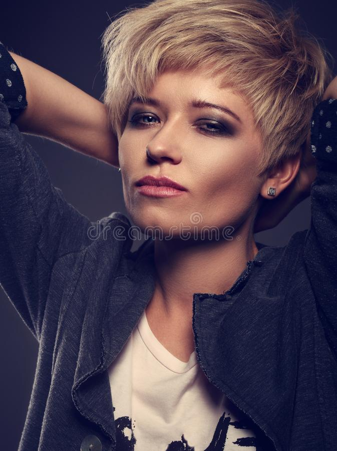 Beautiful cocky woman with short bob blond hairstyle and bl. Ack smoky eyeshadow makeup in fashion jacket on grey background. Closeup toned portrait royalty free stock photo
