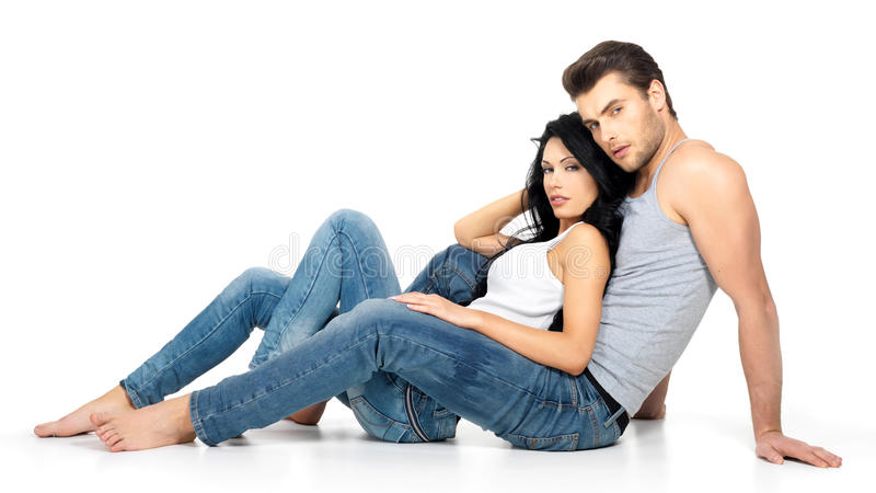 Beautiful couple in love. On white background dressed in blue jeanse and white undershirt royalty free stock photography