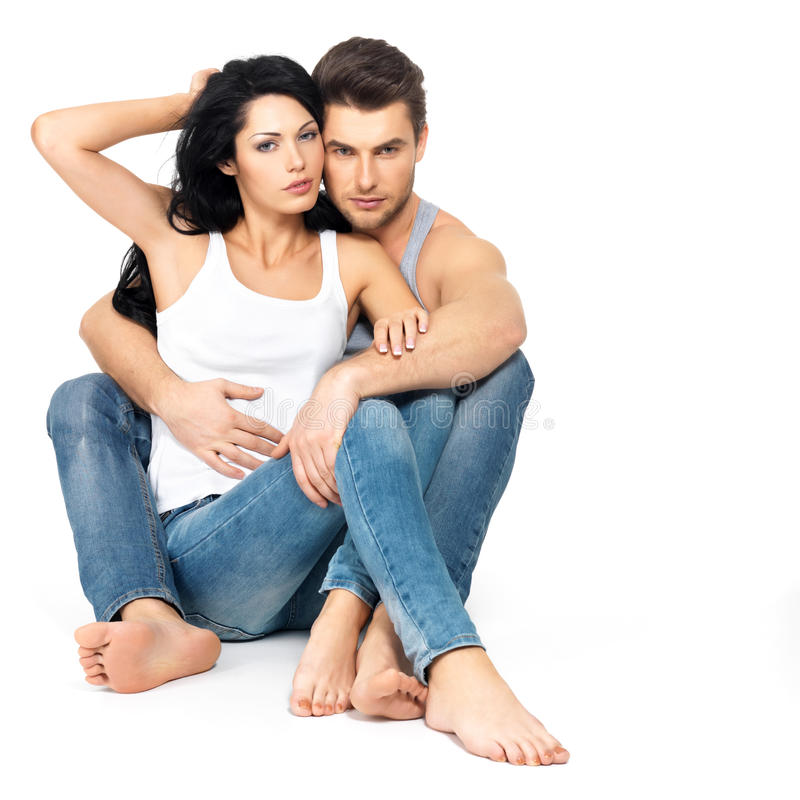 Beautiful couple in love. On white background dressed in blue jeanse and white undershirt stock photo