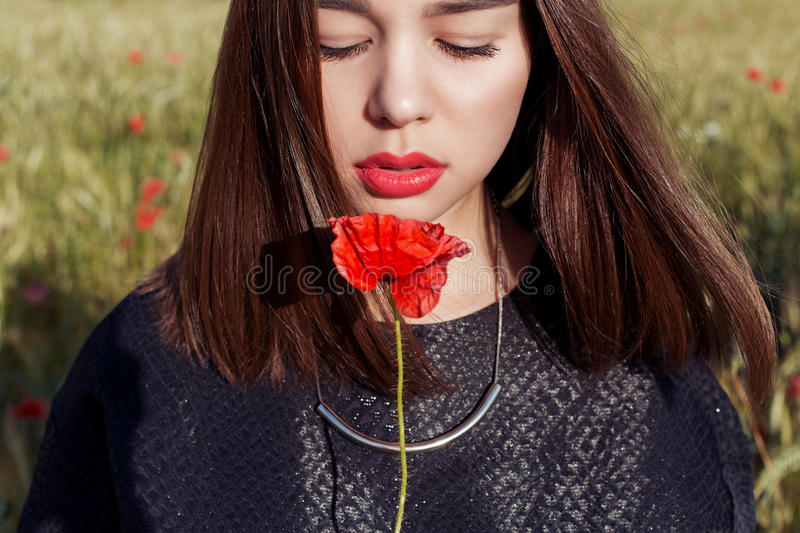 Beautiful cute girl with big lips and red lipstick in a black jacket with a flower poppy standing in a poppy field at sunset royalty free stock images