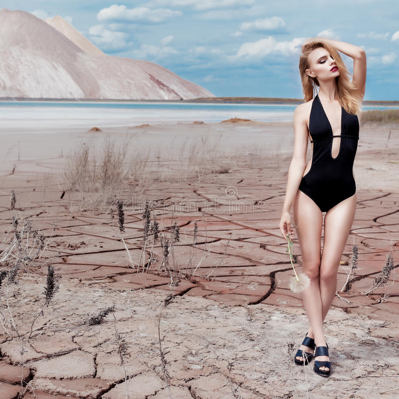 Beautiful cute girl in swimsuit fashion shoot in desert with dry cracked ground background mountains under royalty free stock photography